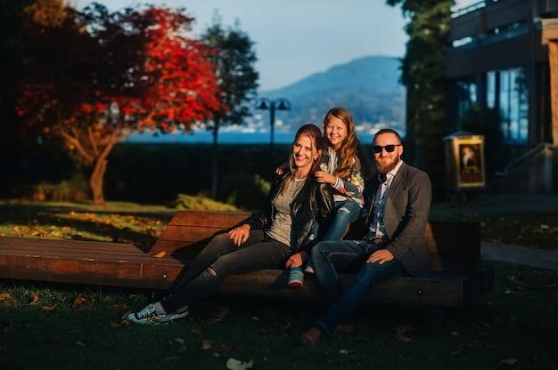 オーストリアの旧市街の晴れた秋の夕日のベンチに座っている3人の幸せな家族。オーストリアのアルプスを背景に小さなオーストリアの町でポーズをとる家族。ヨーロッパ。フェルデン・アム・ゼー
