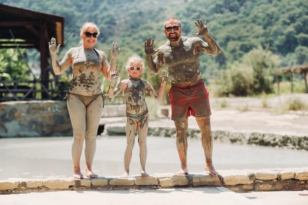 터키의 한 리조트에서 세 명의 행복한 가족이 진흙 목욕을합니다.