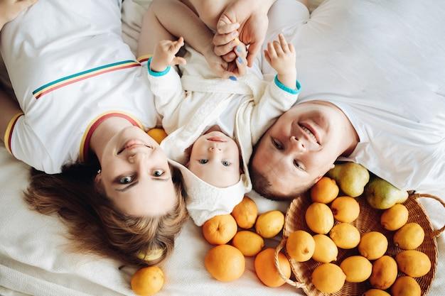 Счастливая семья из трех человек любит разные фрукты, лежит на диване и наслаждается совместной жизнью.