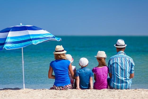 自然旅行で海のそばに子供を持つ幸せな家族の両親