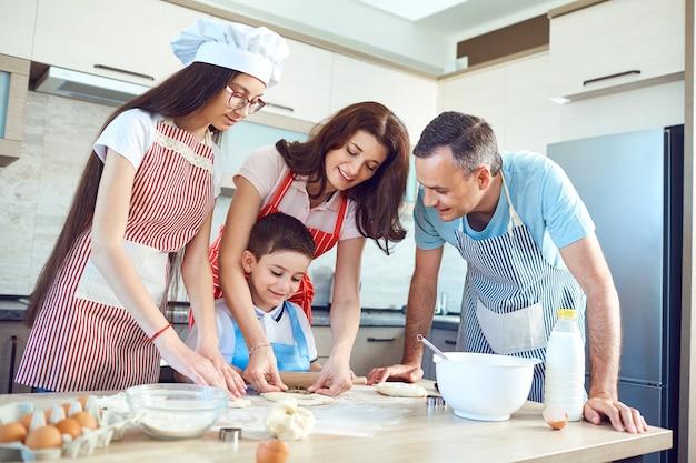 행복한 가족이 부엌에서 베이킹을 준비합니다.