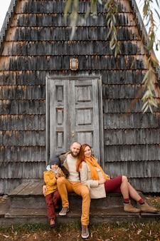 幸せな家族が家の入り口の前の階段に座っています。