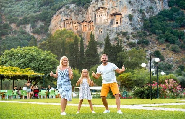 ダルヤン市の山を背景に幸せな家族が立っています。トルコのリュキアの墓の近くの人々。