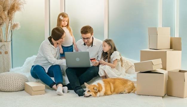 행복한 가정은 온라인 쇼핑을 위해 노트북을 사용합니다. 집에 앉아있는 부모는 온라인 쇼핑을 위해 신용 카드를 사용합니다.