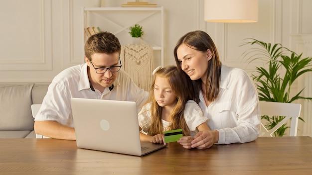 행복한 가족은 집에 앉아 온라인 쇼핑을 위해 노트북을 사용합니다.