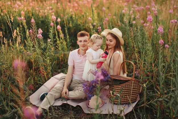 幸せな家族が花の牧草地を歩きます。愛と春の開花