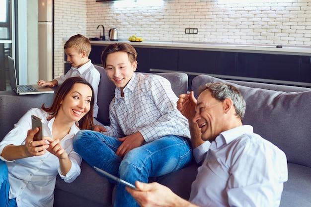노트북과 함께 행복한 가족이 방에서 재미를 즐기고 있습니다.