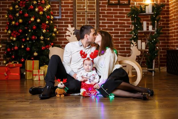 小さな子供を持つ幸せな家族は、おもちゃや贈り物を持ってクリスマスツリーの近くに立っています。幸せな子供時代。お正月のお祭りの雰囲気。家族関係の概念