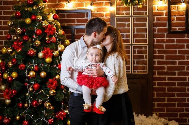Счастливая семья с маленьким ребенком стоит возле елки с игрушками и подарками. счастливое детство. новогодняя праздничная атмосфера. концепция семейных отношений