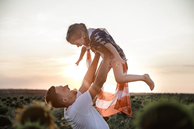 日没時にアメリカの国旗を持つ幸せな家族。