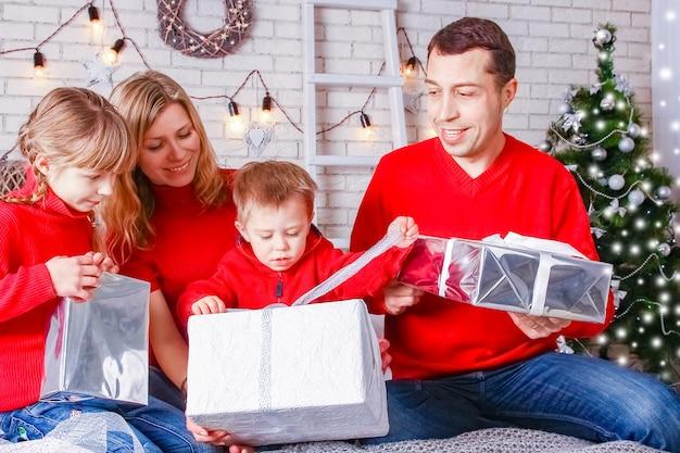 クリスマスに贈り物を持って幸せな家族