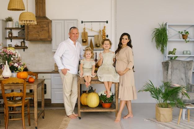 2人の子供を持つ幸せな家族が台所の家にいます。美しく装飾された家の水平方向の肖像画