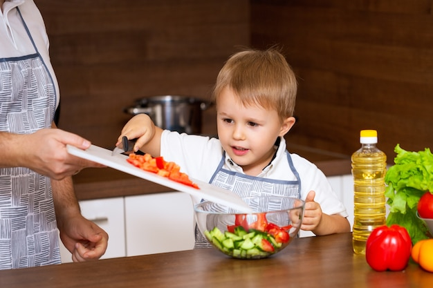 幸せな父と幼い息子が野菜を使ってキッチンでサラダを準備します。私の父は黒板にトマトを切る方法を教えてくれます。ダイエット食品のコンセプト