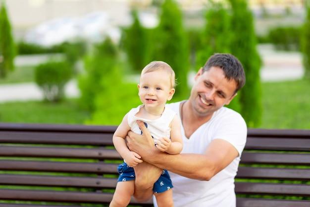 공원에 아들을 안고 있는 행복한 아버지가 야외 벤치에 앉아 팔에 아기를 안고 즐거운 시간을 보내고 있습니다.