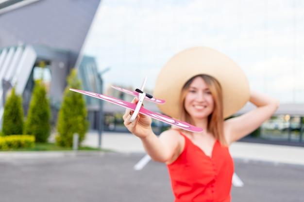 공항에 있는 행복한 소녀는 여름에 빨간 드레스와 모자를 쓴 비행기를 손에 들고 여행이나 휴가의 개념, 비행기는 초점을 맞춥니다