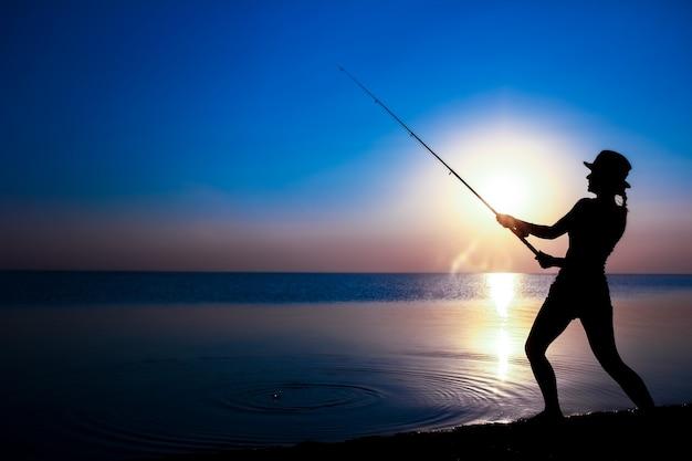 행복한 여자 어부가 자연 실루엣 여행에 바다로 물고기를 잡는