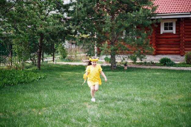 민들레 화환이 달린 드레스를 입은 행복한 소녀가 잔디밭에서 뛰고 있다. 소녀는 현지 여행에서 행복하다
