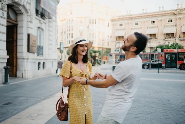 Счастливая девушка в шляпе и желтом платье с глубоким вырезом танцует с парнем с бородой и солнцезащитными очками в старом городе.