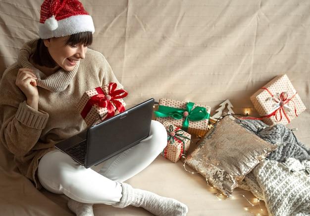 스웨터에 행복한 소녀는 아늑한 장식 벽에 그녀의 손에 선물 상자가있는 노트북 화면 앞에 앉아 있습니다. 온라인 선물 및 거리주는 선택의 개념.