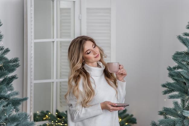 Счастливая девушка в теплом зимнем свитере стоит на кухне в скандинавском стиле и пьет горячий напиток из розовой чашки у елки. новогоднее утро. праздничный интерьер и украшение дома.