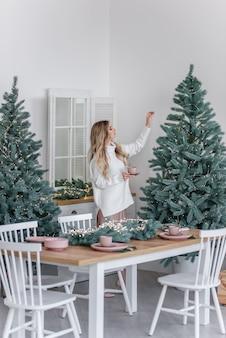 暖かい冬のセーターを着た幸せな女の子がスカンジナビアスタイルのキッチンに立って、クリスマスツリーのそばのピンクのカップから温かい飲み物を飲みます。新年の朝。お祝いのインテリアと家の装飾。