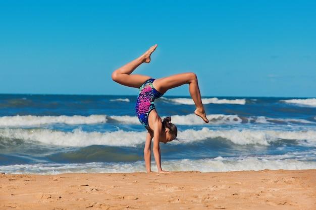 행복한 소녀가 바다를 배경으로 모래 위에 손을 대고 비틀거리고 있다
