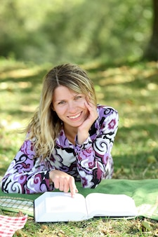 ピクニックで聖書の本を読んで幸せな女の子