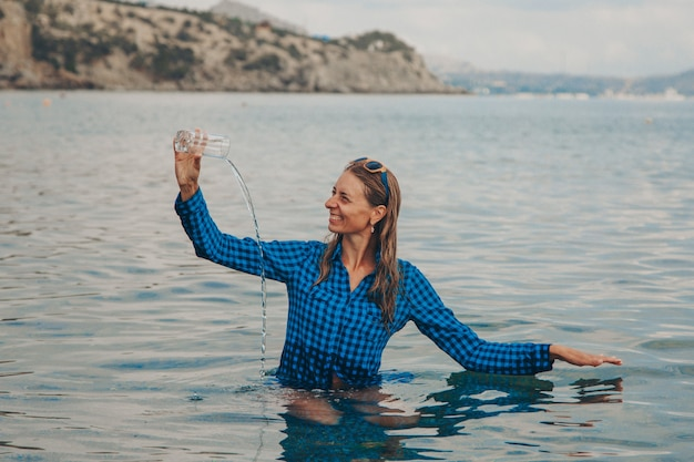 Счастливая девушка сидит в реке и пьет воду из стакана. концепция чистых природных источников, охрана окружающей среды