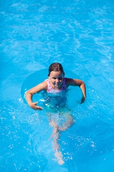 幸せな女の子はコピースペースで水上で安全のために膨脹可能な円のプールで泳ぐ