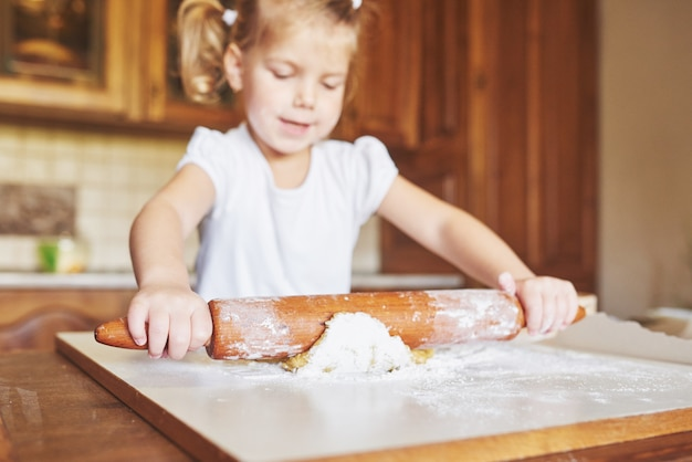 幸せな女の子が生地を着ています。赤ちゃんはシェフのスーツでディナーを作る