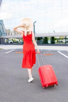 빨간 드레스와 모자를 쓰고 공항에서 여행가방을 든 행복한 소녀는 여름에 여행이나 휴가를 갑니다.