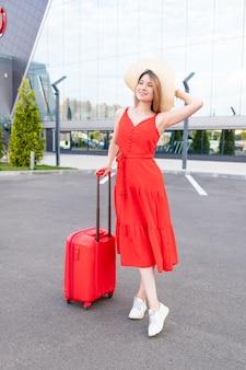 빨간 드레스와 모자를 쓰고 공항에 여행가방을 든 행복한 소녀는 여름에 여행이나 휴가를 간다