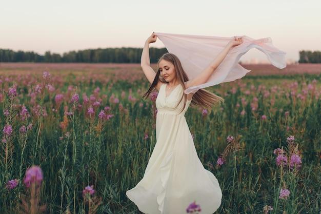 白いスカーフを持つ幸せな女の子が花の牧草地を歩きます。愛と春の開花