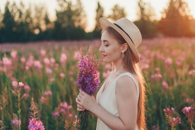 花束を持つ幸せな女の子は、花の牧草地を歩きます。愛と春の開花