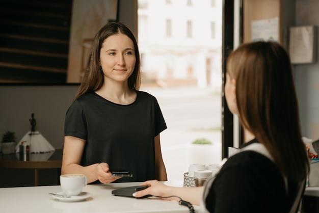 Счастливая девушка с длинными волосами платит за кофе с помощью смартфона по бесконтактной технологии nfc в кафе. брюнетка-бариста протягивает клиенту терминал для оплаты.