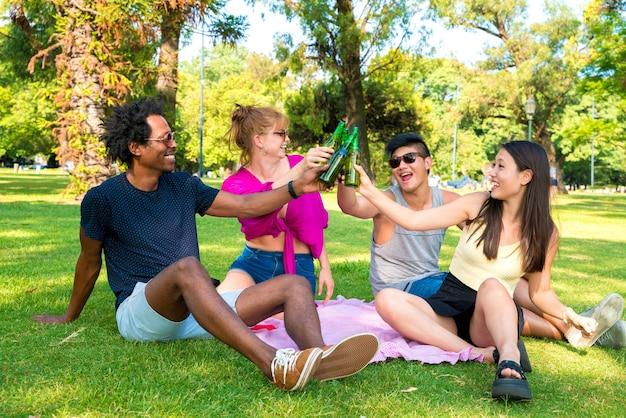 公園で晴れた日を一緒に楽しんでいる友人の幸せなグループ