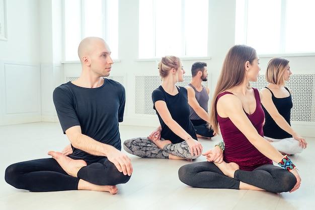 스튜디오에서 요가를 연습하는 남성과 여성의 행복한 그룹. 명상 및 커뮤니케이션 요가 수업 그룹. 그룹 명상과 팀워크의 개념. 안티 스트레스의 개념