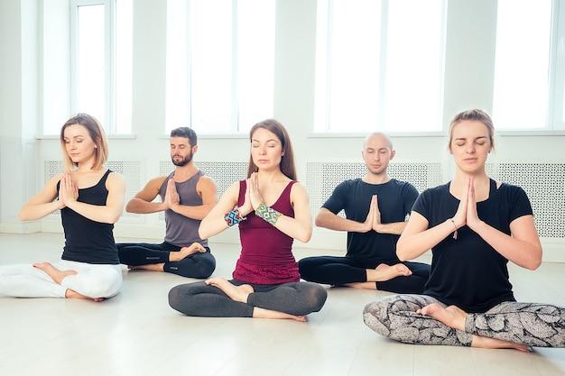 스튜디오에서 요가를 연습하는 남성과 여성의 행복한 그룹. 명상 그룹, 커뮤니케이션 요가 수업. 그룹 명상과 팀워크의 개념. 원의 코치와 학생.