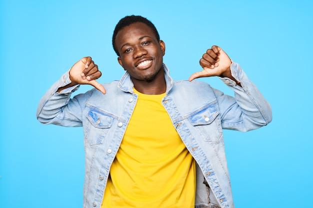 Счастливый парень африканской внешности улыбается и показывает пальцем