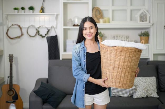 幸せな家政婦が家で洗濯用のバケツ布を運んでいます。