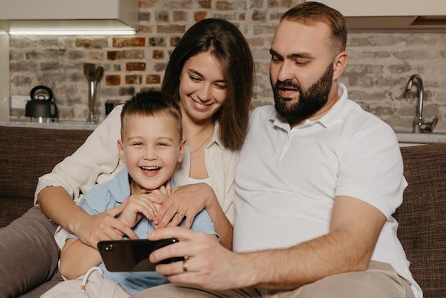 수염을 가진 행복한 남편이 웃는 아이와 아내에게 스마트 폰으로 쇼를 시연하고 있습니다.