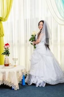 幸せなユダヤ人の花嫁は、白いバラの花束を手に花を持ったテーブルで、フッパー式の前にホールに立っています。