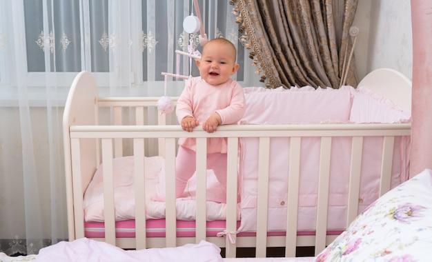 Счастливый, смеющийся ребенок в кроватке в розовой спальне.
