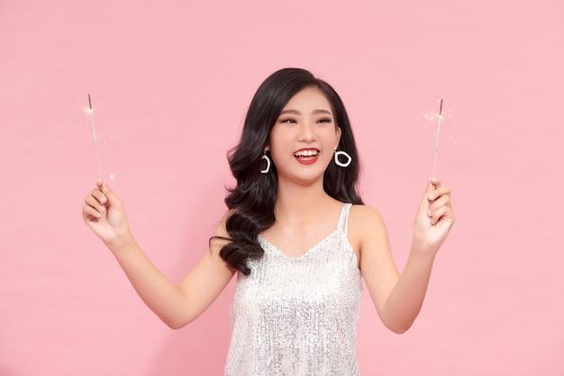 彼女の手に線香花火とスパンコールと銀のイブニングドレスで幸せな笑う美しい女性モデル