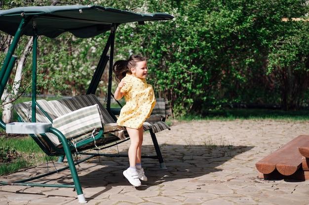 정원 그네에서 뛰어내리는 행복한 웃는 소녀 소녀는 뒤뜰과 그네에서 즐거운 시간을 보내고...