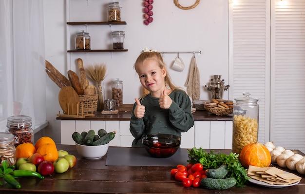 행복한 금발 소녀가 야채와 과일이 있는 부엌 테이블에 앉아 있다