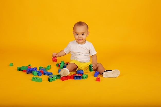 흰색 티셔츠와 노란색 반바지를 입은 행복한 소년이 레고를 하고 있다