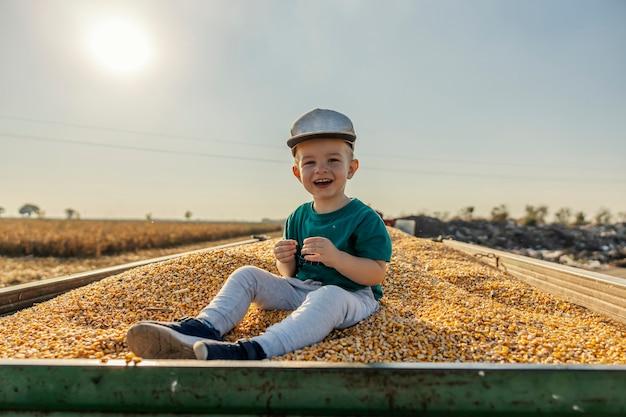 행복한 어린 소년이 옥수수 곡물로 가득 찬 트랙터에 앉아 카메라를 바라보면서 곡물을 손에 들고 있습니다. 수확을 돕는 농부 소년