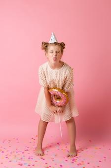 誕生日の帽子をかぶった幸せな少女は、スタジオでピンクの背景にドーナツ型の風船を持っています