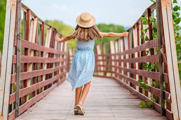 Счастливая маленькая девочка в синем платье в летнем саду с деревянным мостиком